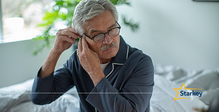 Elderly man in dark grey pajamas sitting on a bed, putting a hearing aid on his right ear